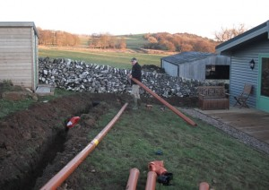 David installing sewage pipes for Daisybank log cabin