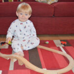 baby playing with trainset